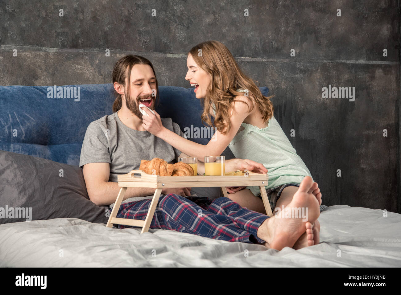 Young woman feeds her boyfriend with breakfast in bed - Stock Image