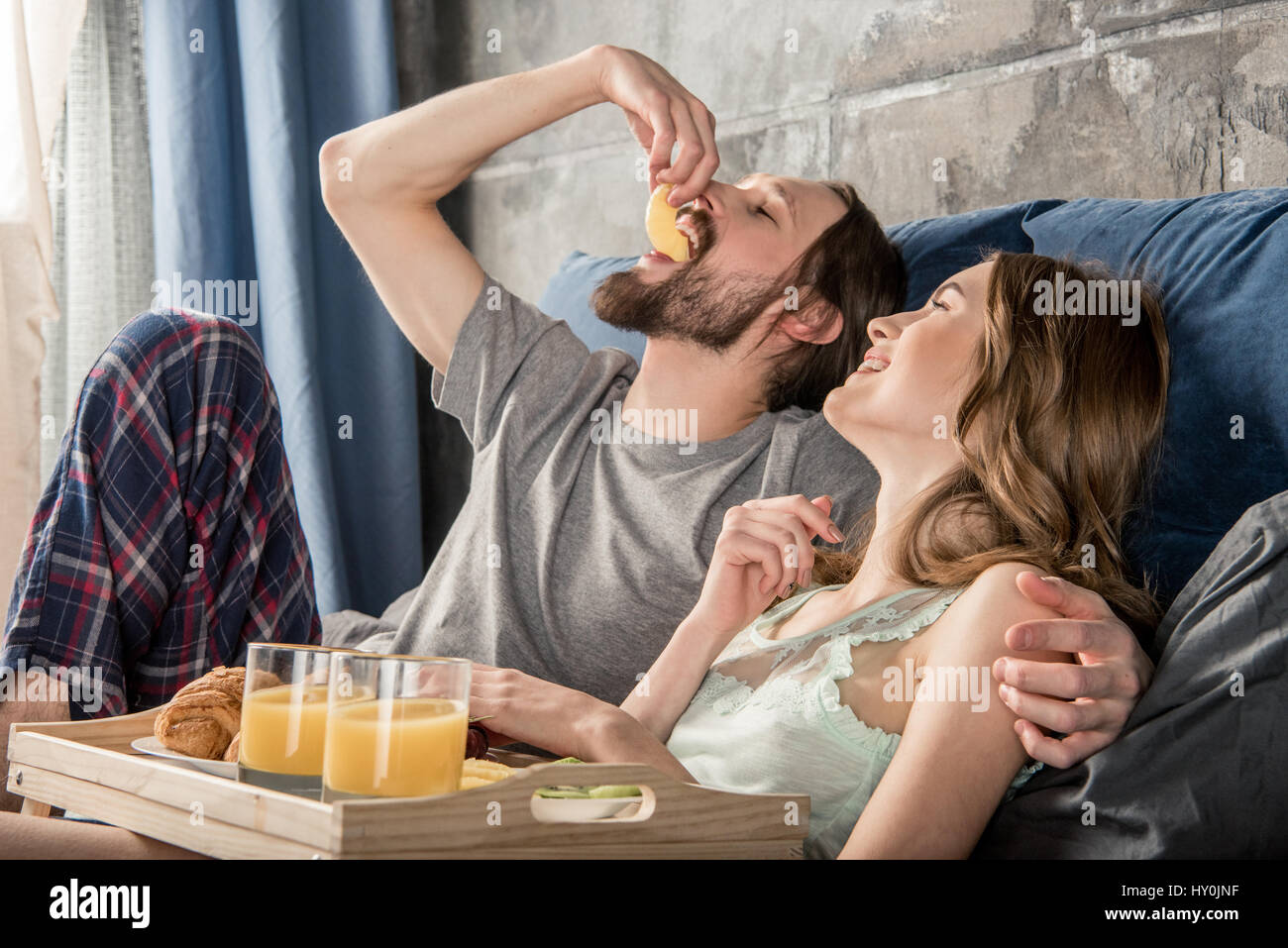 Young relaxed couple has breakfast in bed - Stock Image