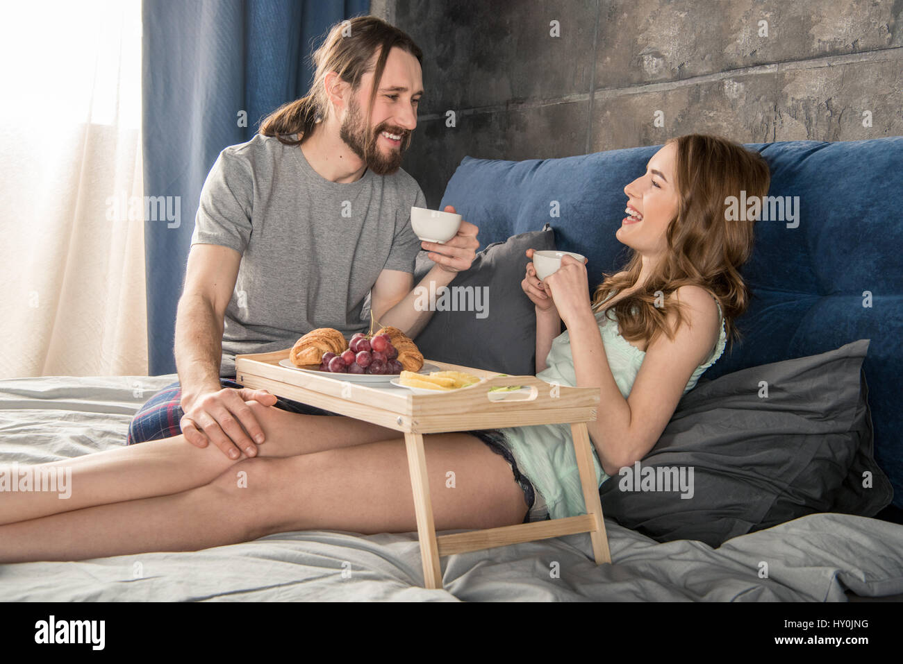 Young relaxed couple has breakfast and drinks coffee while lying in bed - Stock Image