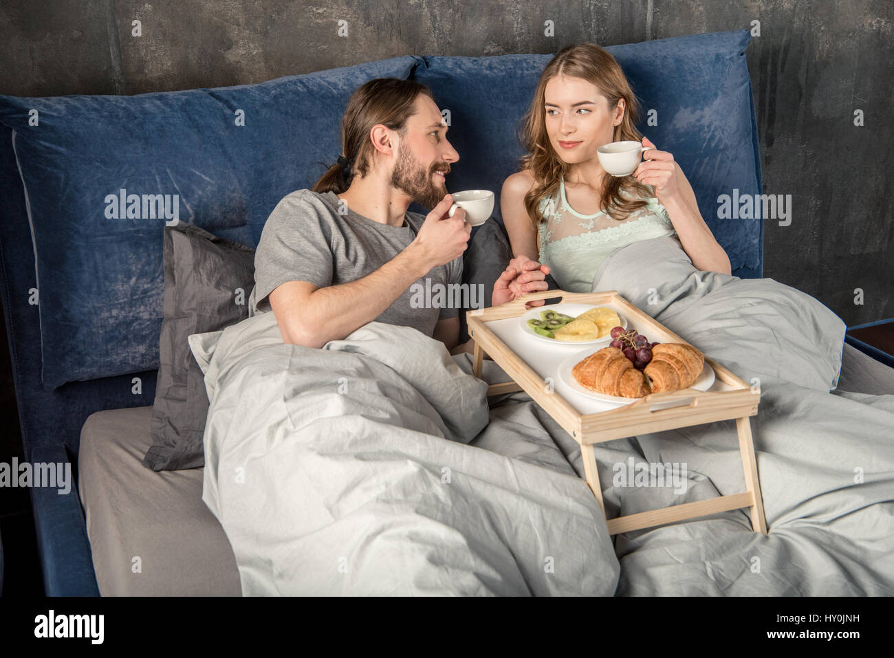 Young happy couple has breakfast in bed and drinks coffee - Stock Image