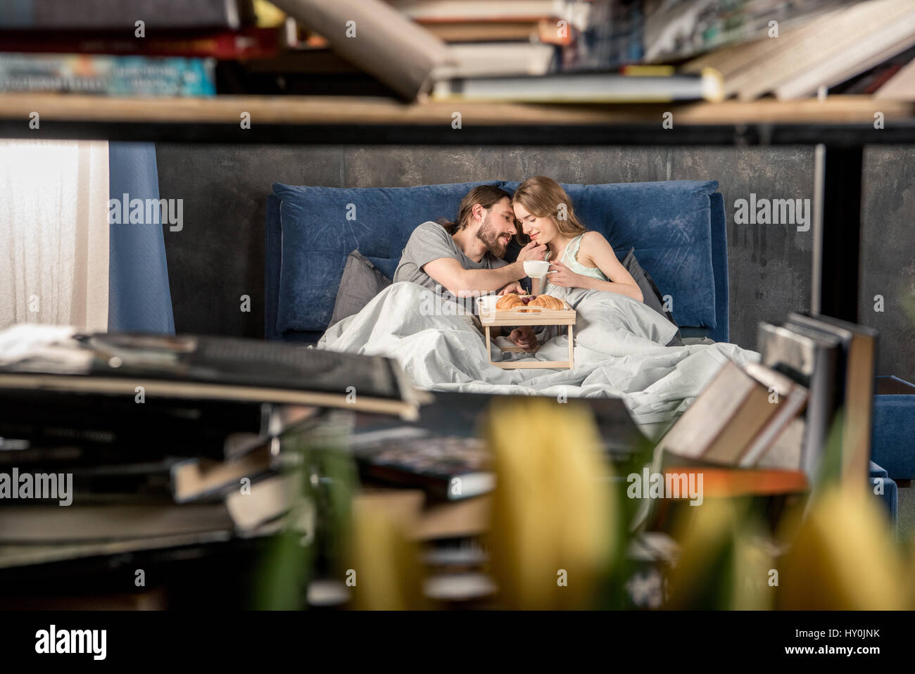 View through the bookshelf of young couple has breakfast in bed - Stock Image