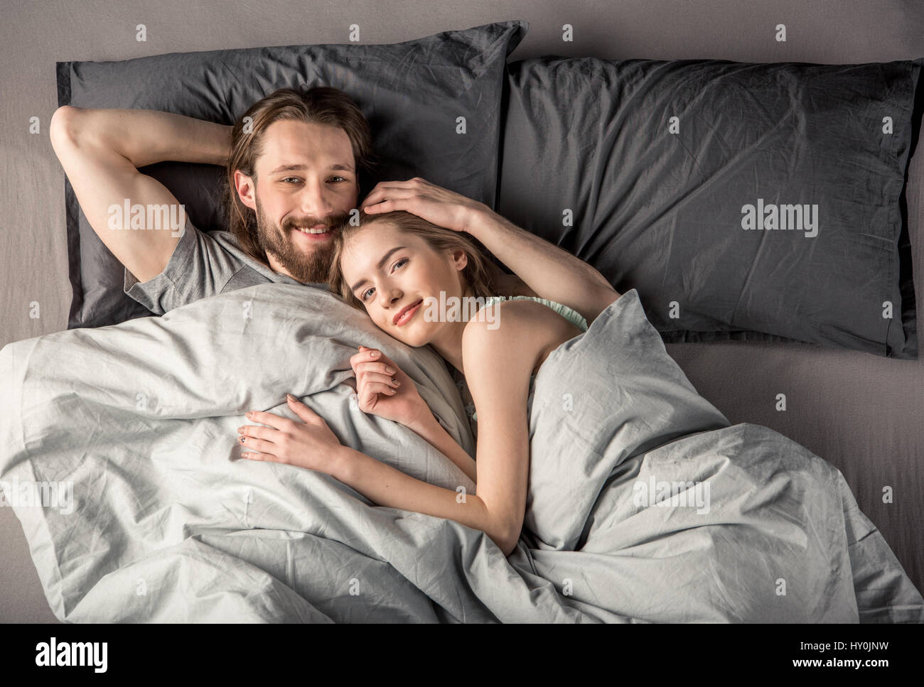 Overhead view of young happy couple in love lying in bed - Stock Image