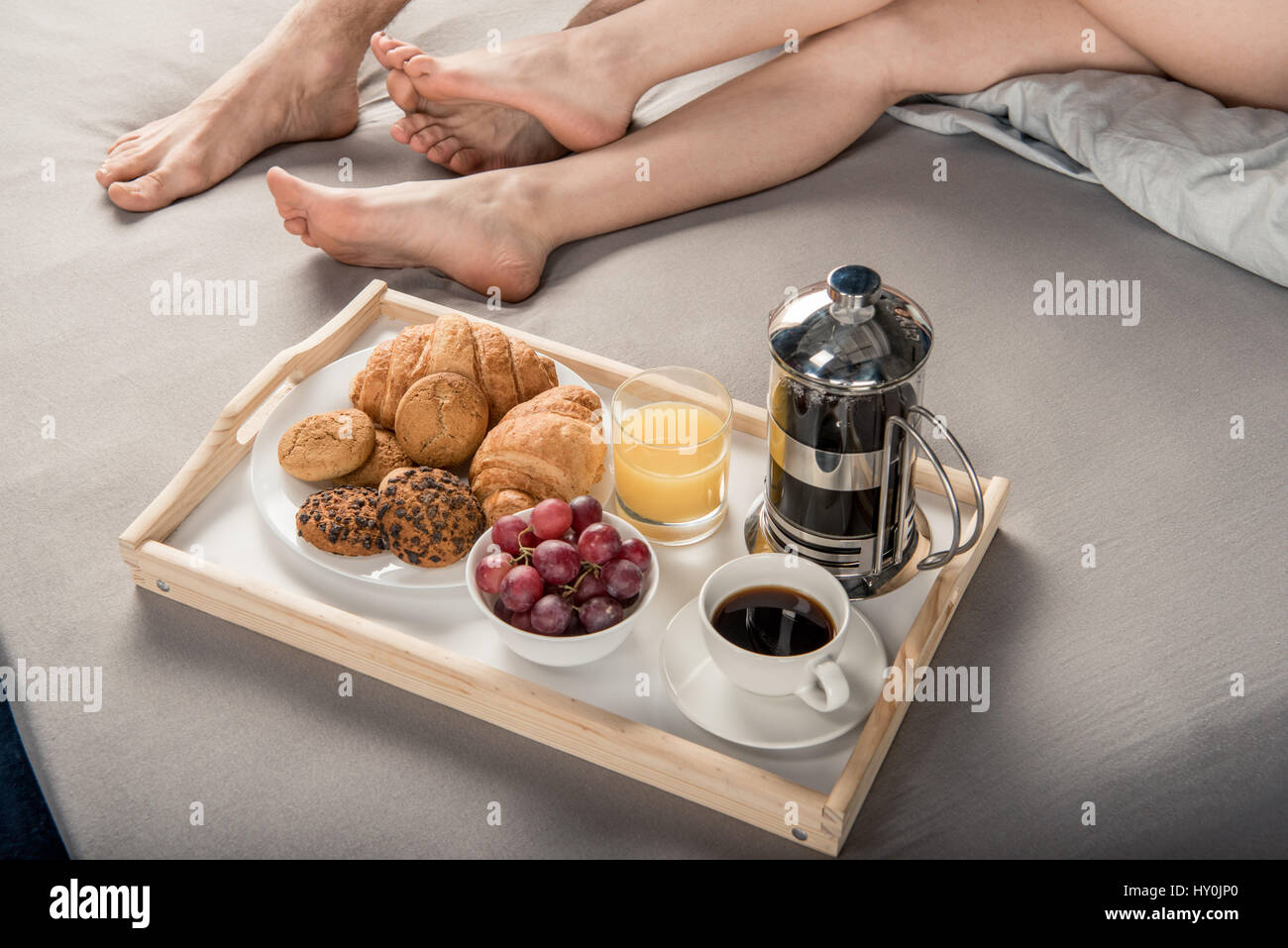 Partial view of male and female legs and breakfast on bad tray - Stock Image