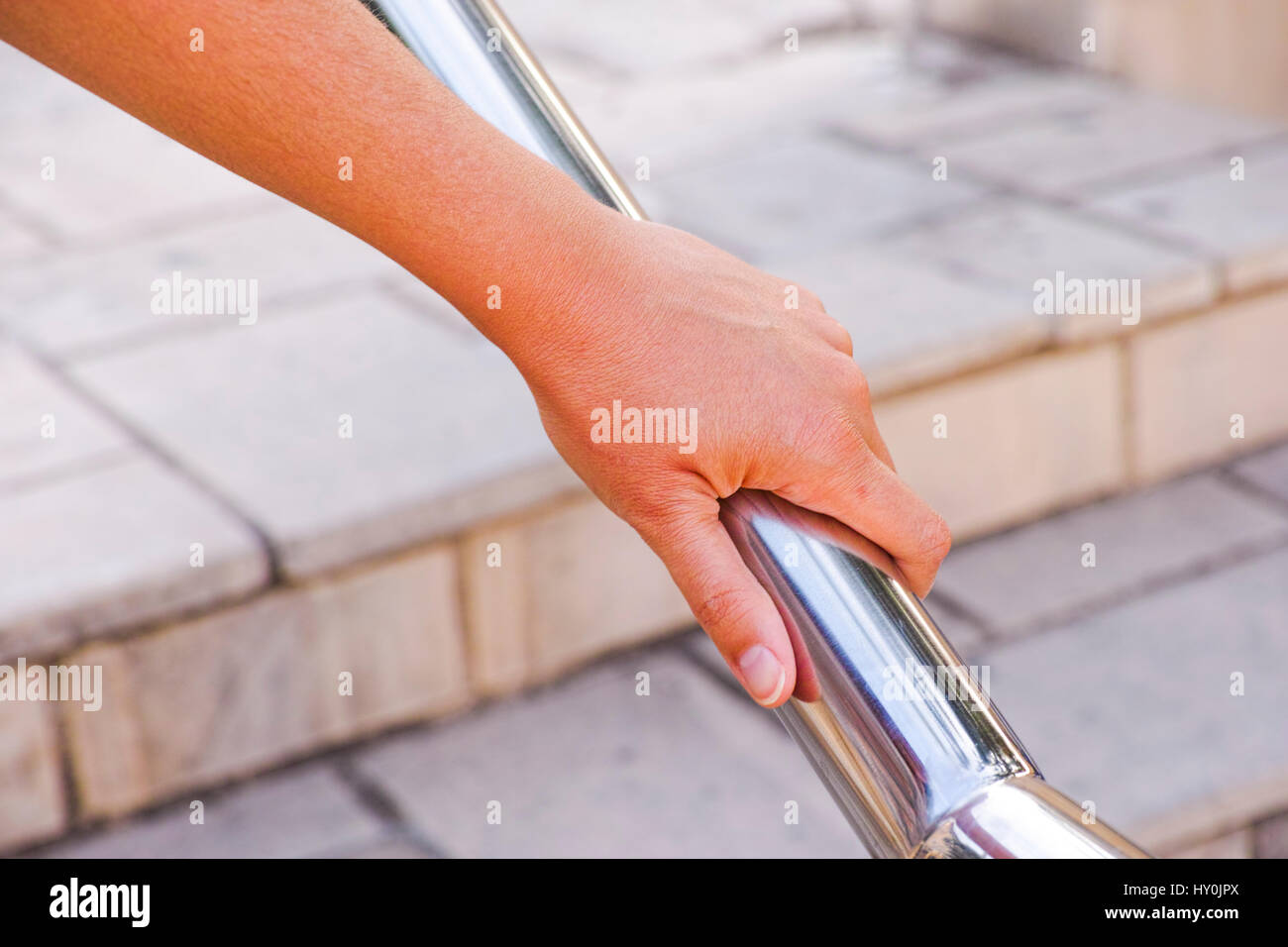 Woman hand using a handrail in the street. - Stock Image