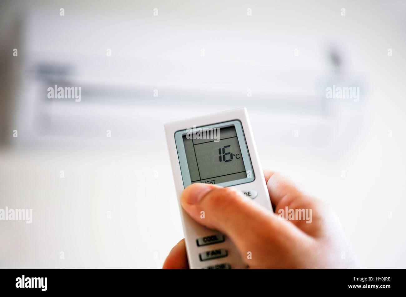Person hand using remote control of air conditioner. - Stock Image