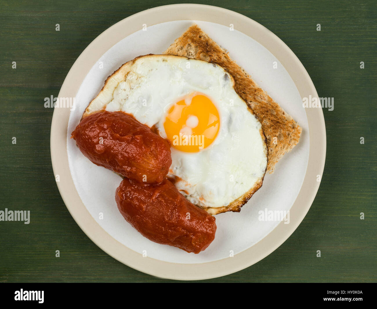 Fried Egg and Tomatoes on Toast on a Plate Against a Green Background Stock Photo