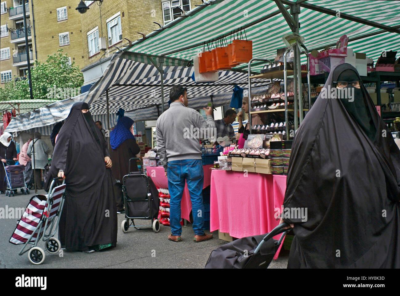 Muslim women in burkas shopping in london market - Stock Image