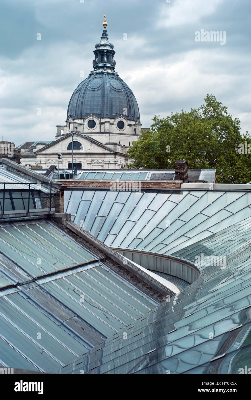 View of Brompton Oratory across new glazed roof reflecting sky clouds and dome and new gallery glass roof at the - Stock Image