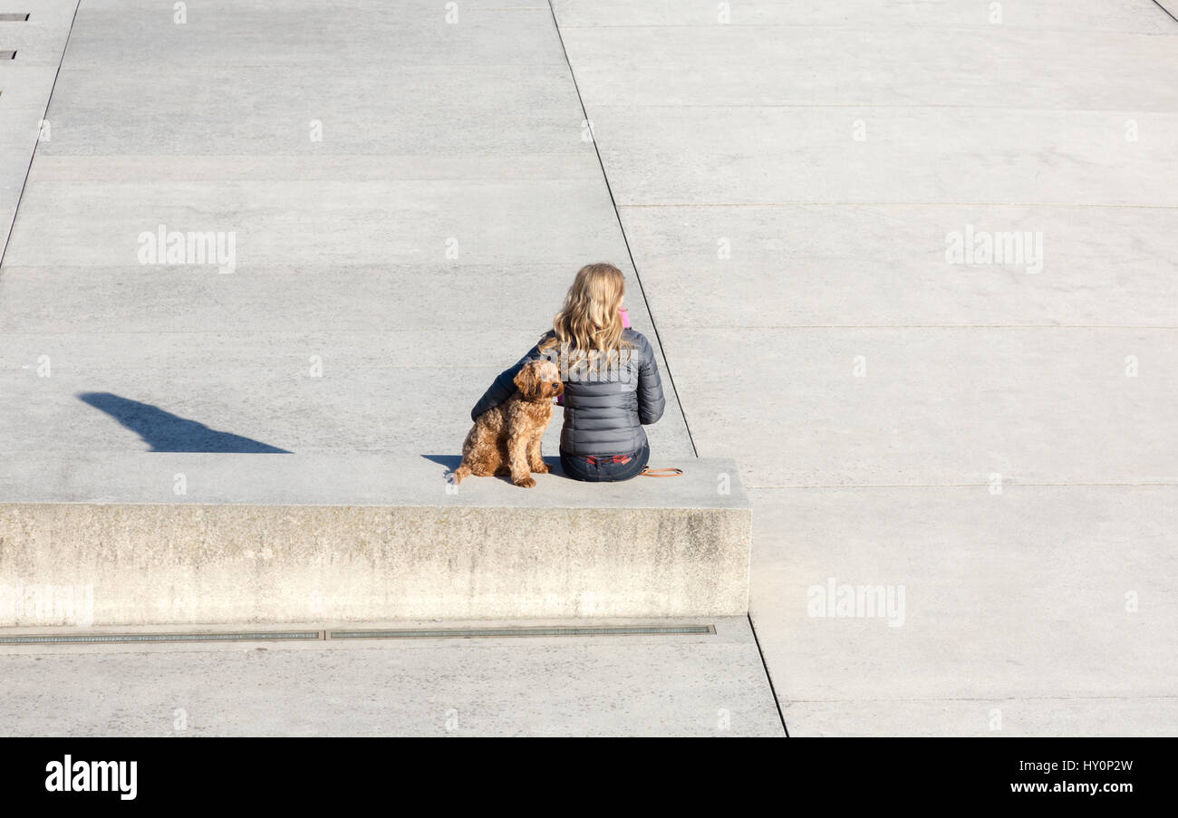 Young attractive woman long blond hair sitting on concrete banch with ginger small cute dog. Horozontal composition - Stock Image