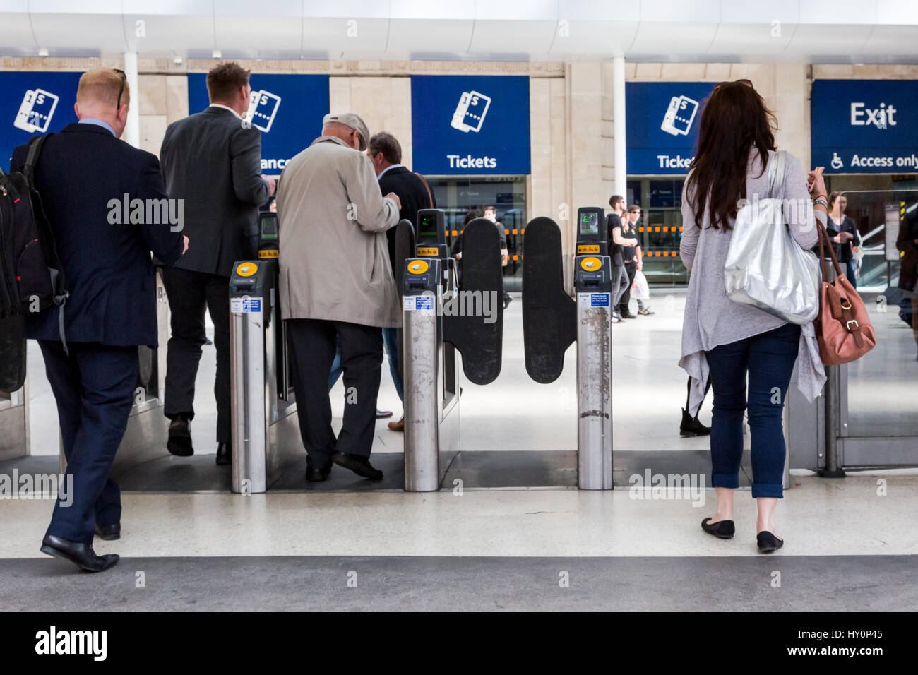 Train passengers go through automatic ticket gates on train station Waterloo in London. Metaphore to Brexit - English - Stock Image