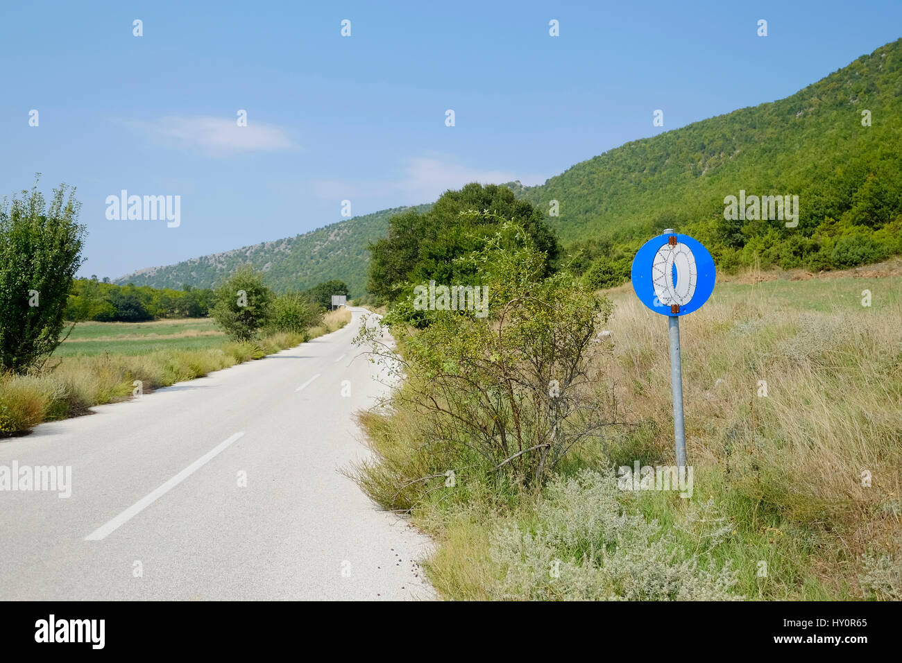 road sign for mounting snow chains is along an overgrown road on a summer day - Stock Image