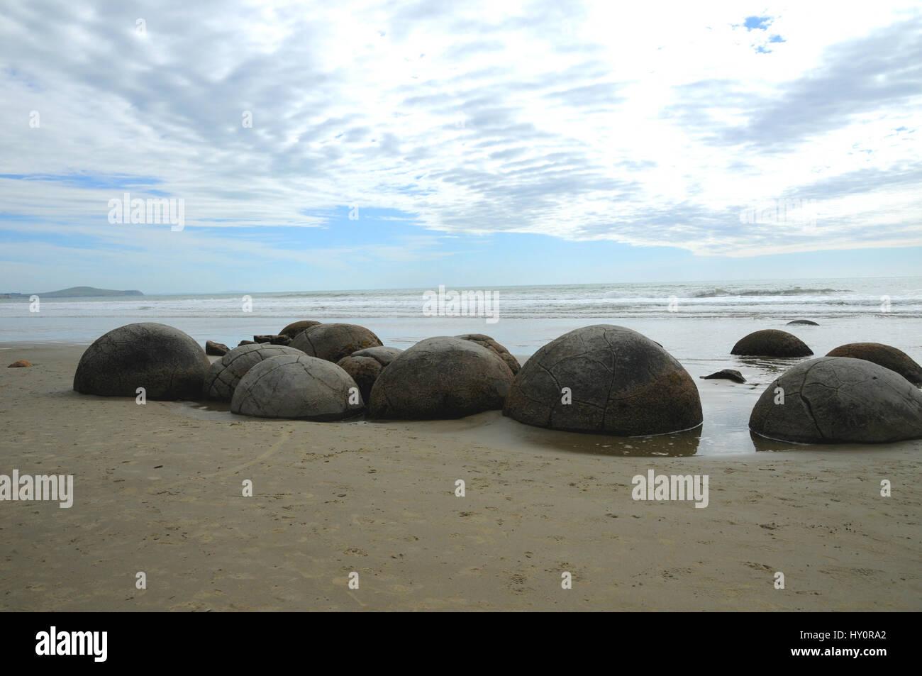 The Moeraki Boulders on Koekohe Beach on the Otago coast of New Zealand's South Island. They are a popular tourist - Stock Image