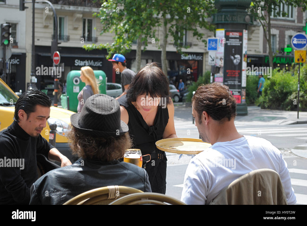 Paris, France, 21 June: A waitress serves visitors a cafe on the Boulevard de Clichy hot sunny day June 21, 2012 - Stock Image