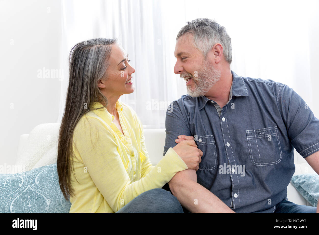 Senior couple at home together on sofa Stock Photo