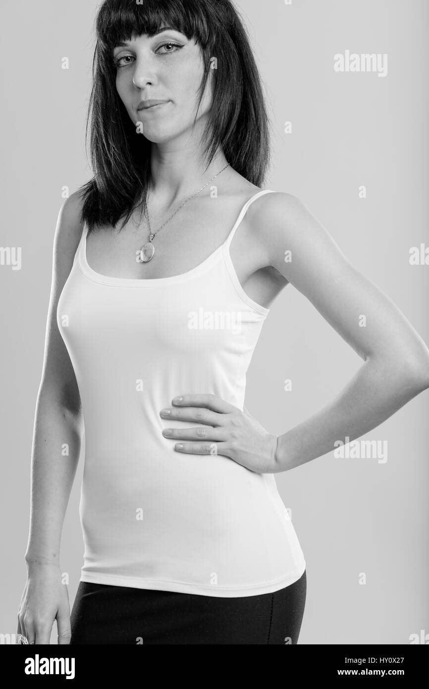 young woman with black hair with a hand on her hip, black and white studio portrait - Stock Image