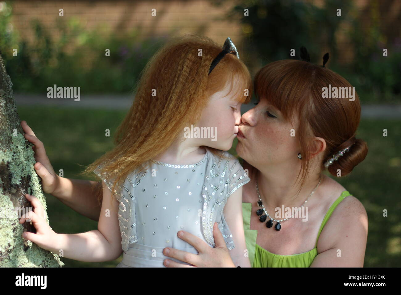 Mother and daughter exchange a loving kiss in the dappled sunlight of a tree  while attending a friend's wedding. - Stock Image