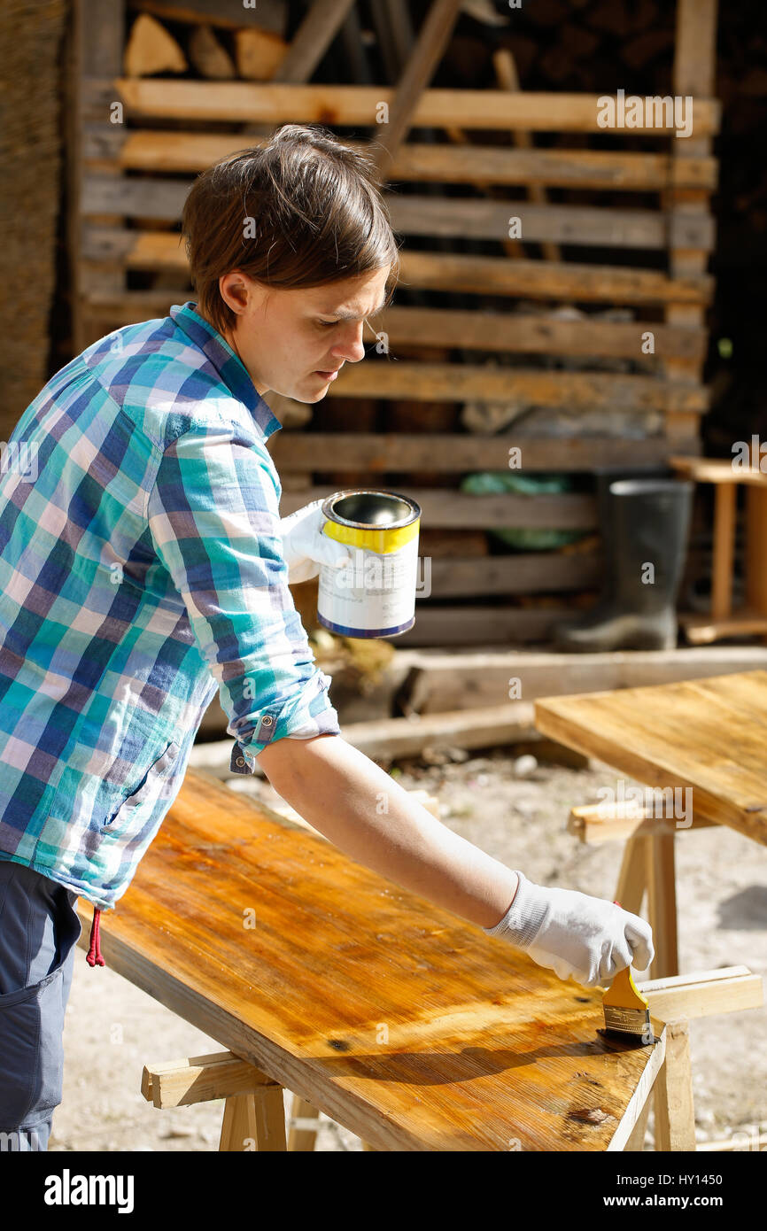 Woman applying and protecting garden furniture with fresh wood Stock ...