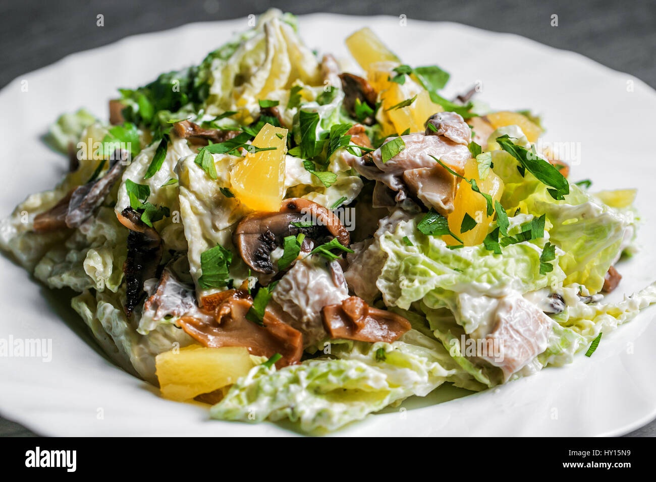 salad with mushrooms and oranges on white plate. selective focus - Stock Image