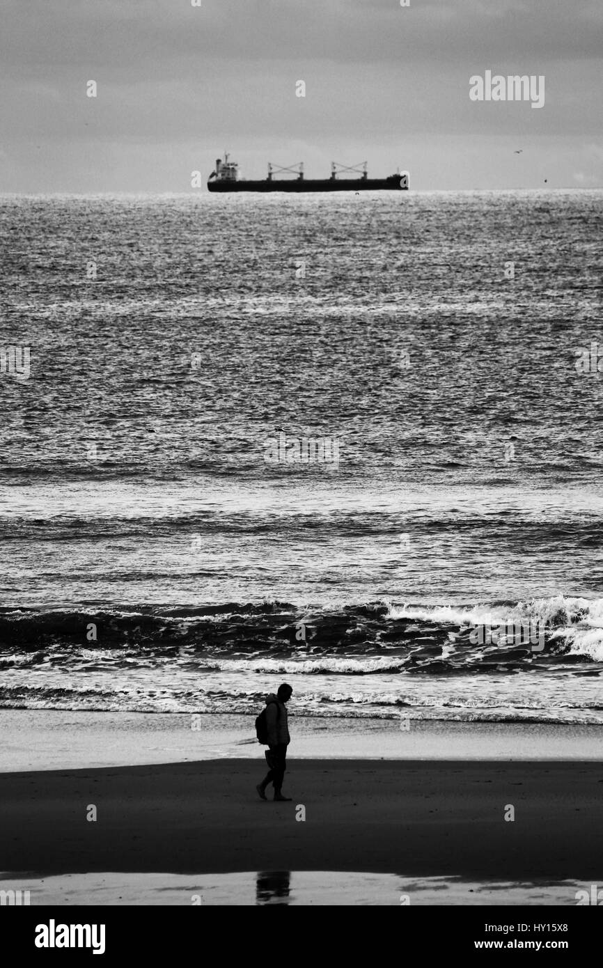 A lonely man walking on the sand of Matosinhos beach while a ship is navigating along the coastline. - Stock Image