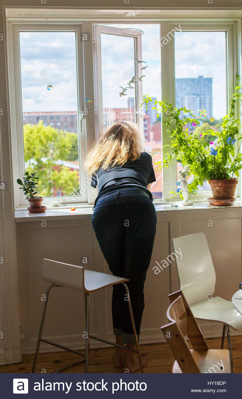 Denmark, Woman looking through window - Stock Image