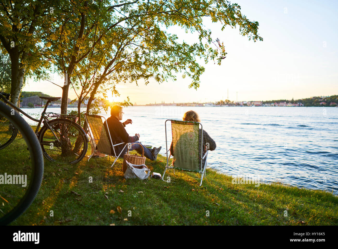 Sweden, Sodermanland, Nacka, Couple sitting on deckchair and relaxing - Stock Image