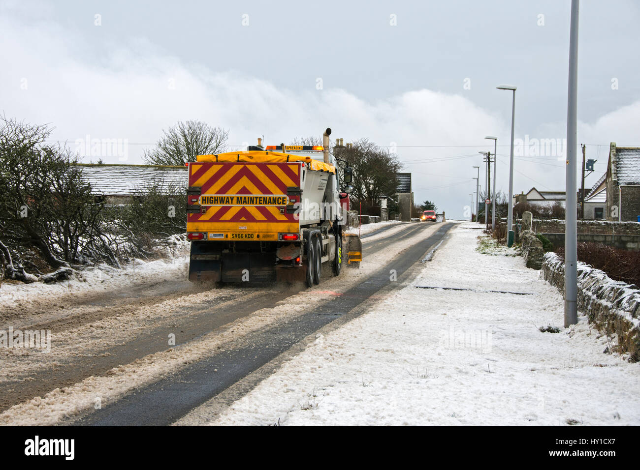 Snow plough - gritter lorry on the A836 trunk road in snowy weather, at the village of Mey, Caithness, Scotland, - Stock Image
