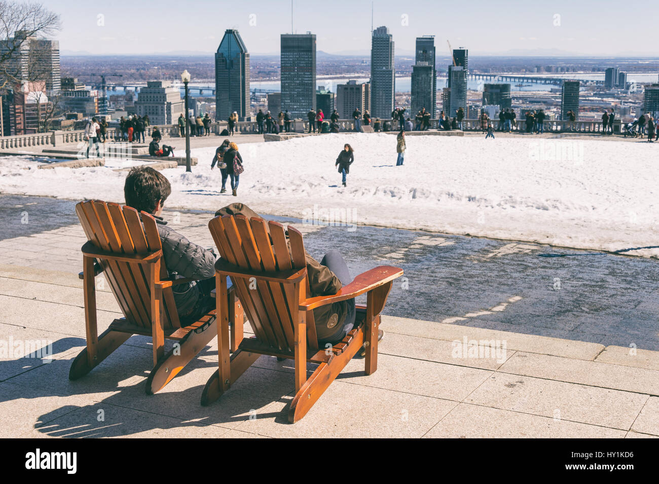 Montreal, CA - 30 March 2017: People sitting on a wooden lawn chair and enjoying a sunny spring day on Kondiaronk Stock Photo
