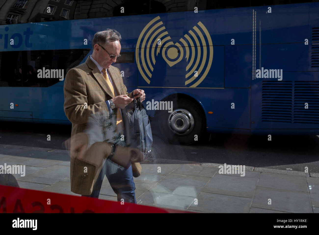 Man checks messages while passing Wifi symbol, on 30th March 2017, in London, England. - Stock Image