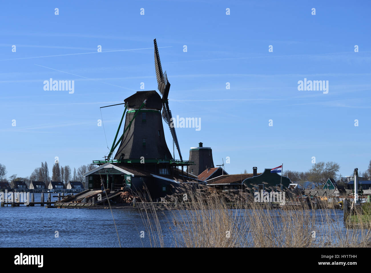 Old style windmill in Dutch countryside on waterway - Stock Image