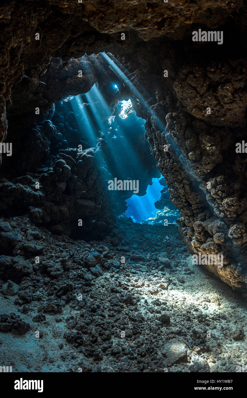 Shafts of light shine through darkness of cavern within  coral reef. Sha'ab Claudia, Fury Shoal, Egypt. Red - Stock Image