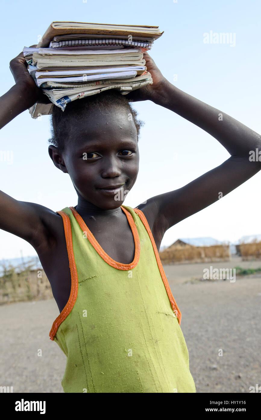 KENYA, Turkana, refugee camp Kakuma IV, south sudanese refugees, girl on way to school carry books on the head  - Stock Image