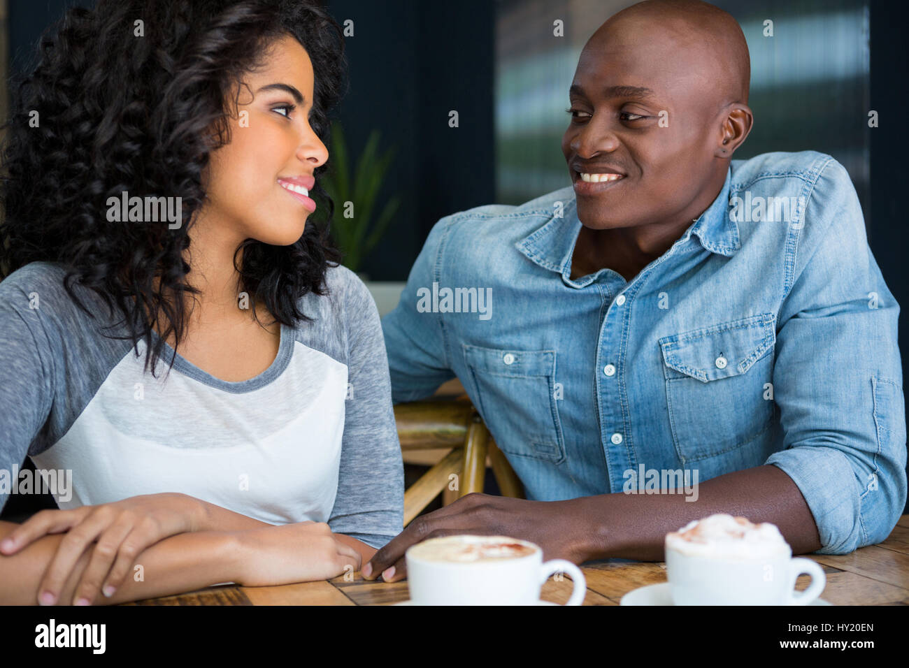 Loving young couple looking at each other at table in coffee shop - Stock Image