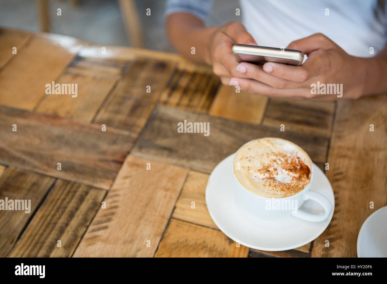 High angle view of woman using mobile phone with coffee cup on table at cafe - Stock Image