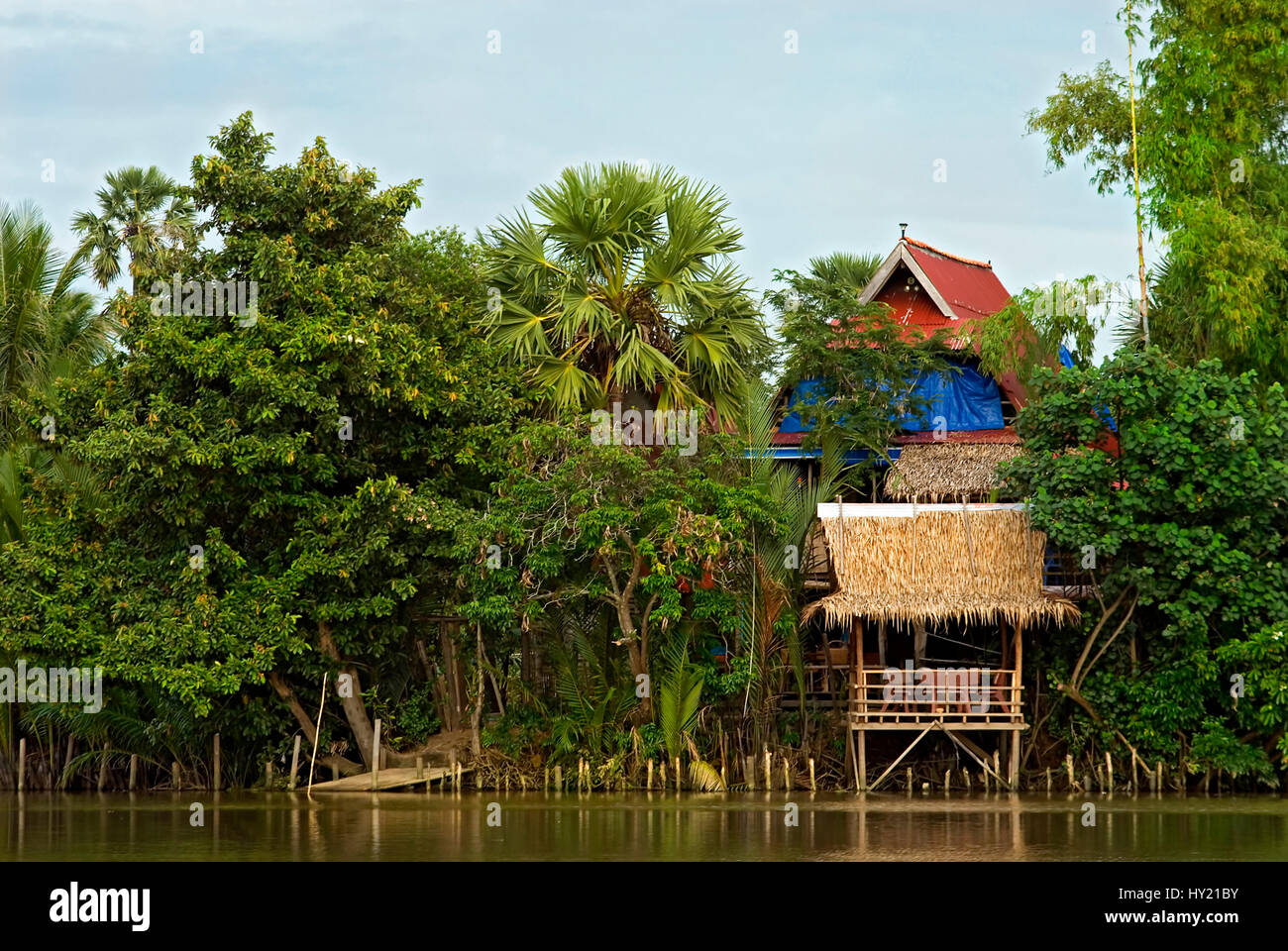 This stock photo shows a colorful wooden fishing hut at the bank of the Kampot Bay River near the city of Kampot Stock Photo