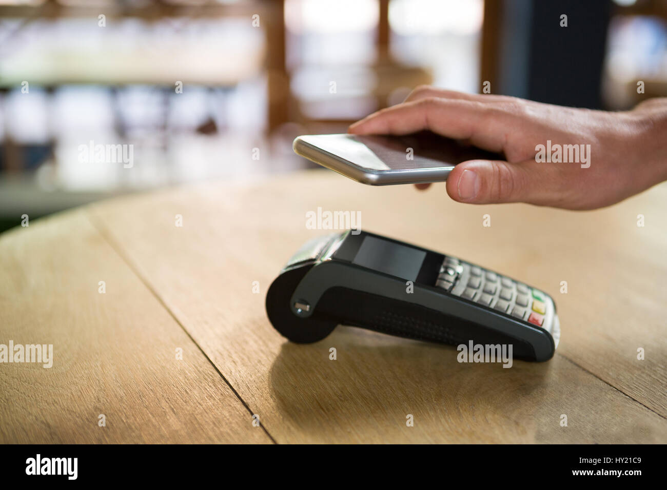 Cropped image of customer hand paying through smart phone in coffee shop Stock Photo