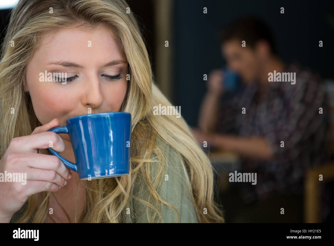 Close-up of young woman drinking coffee in cafeteria Stock Photo