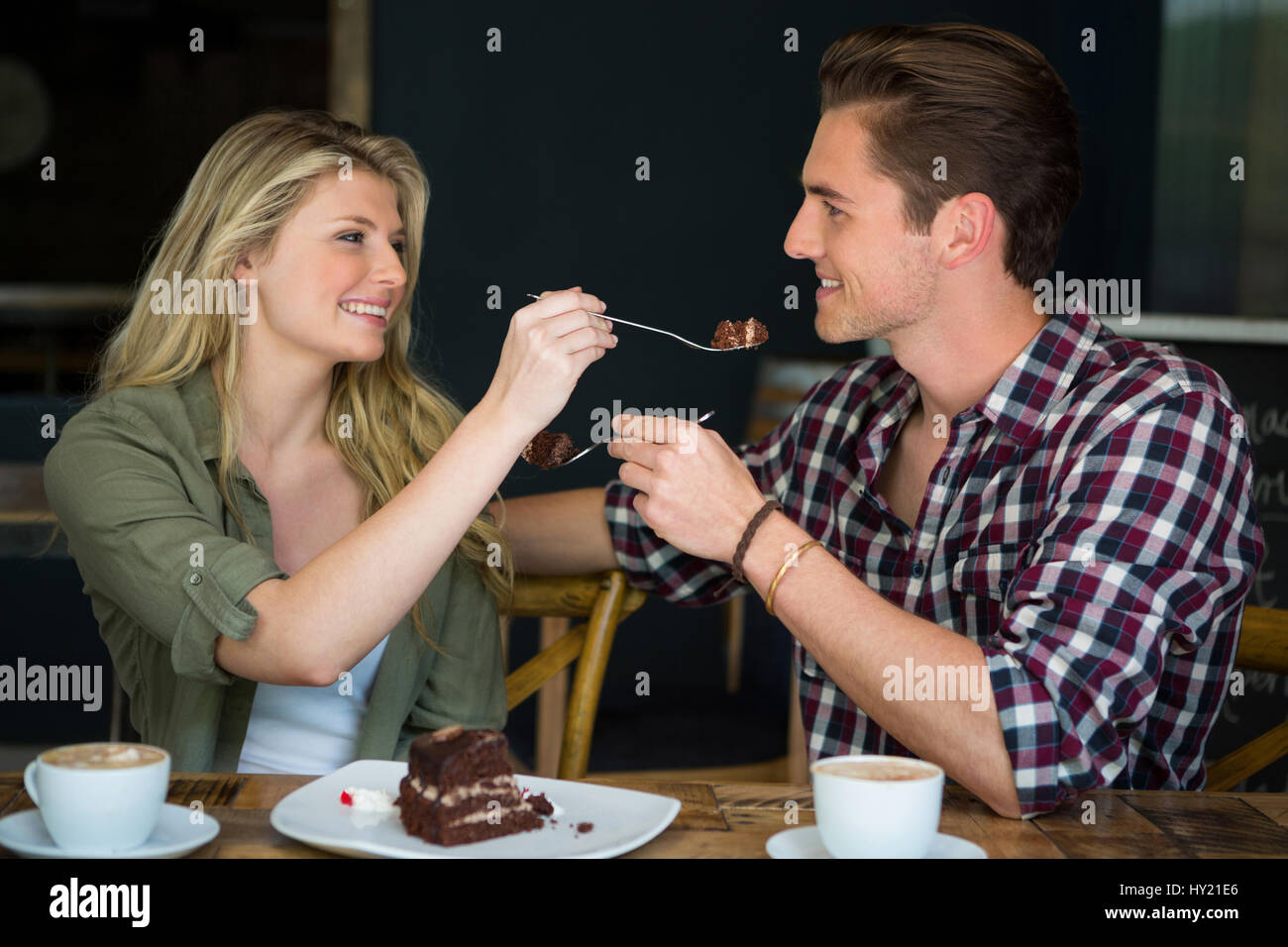 Smiling young couple feeding each other dessert in cafe - Stock Image
