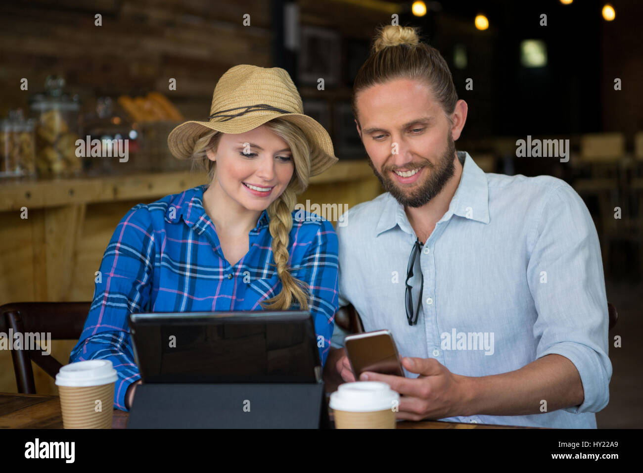 Smiling young couple using mobile phone at table in cafe Stock Photo