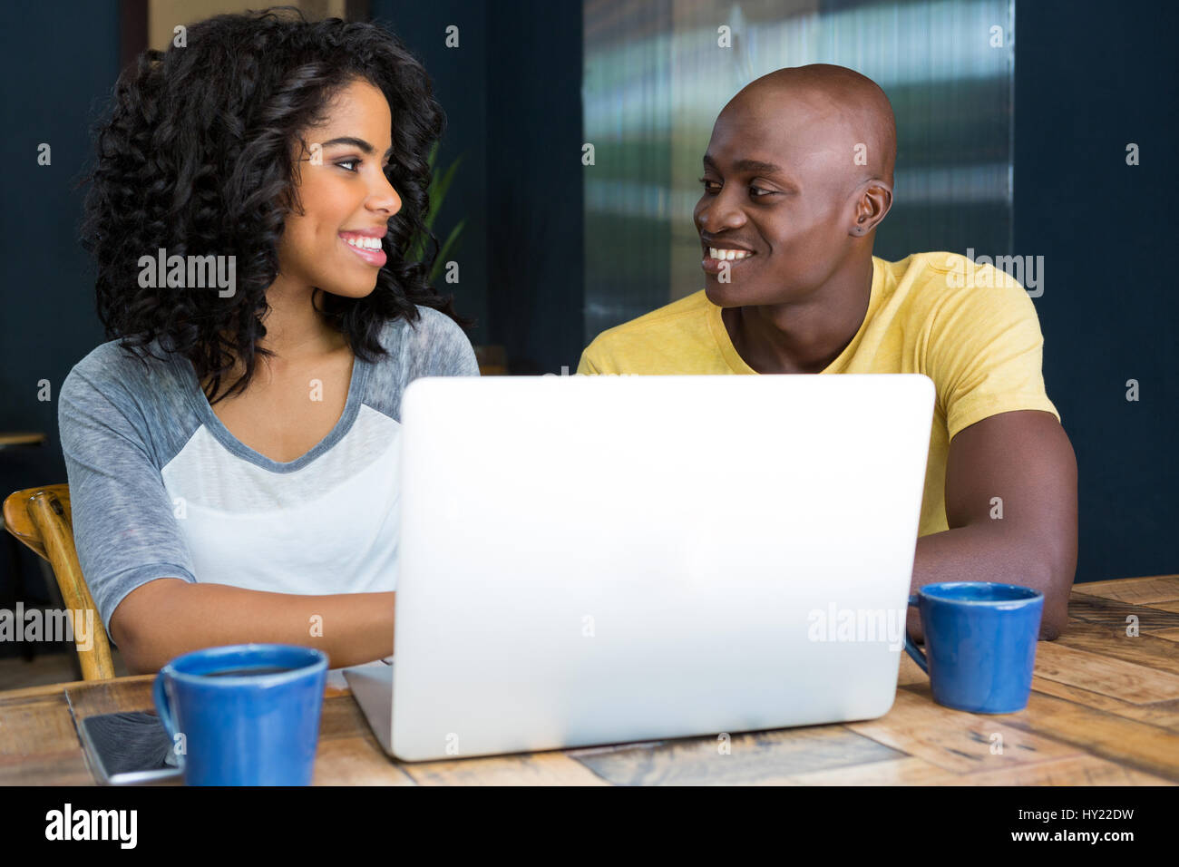 Smiling couple looking at each other with laptop on table in coffee shop - Stock Image