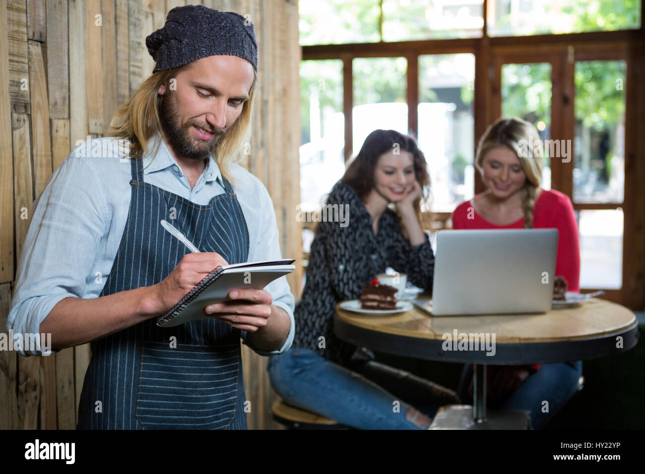 Male barista writing orders with female customers in background at coffee shop - Stock Image