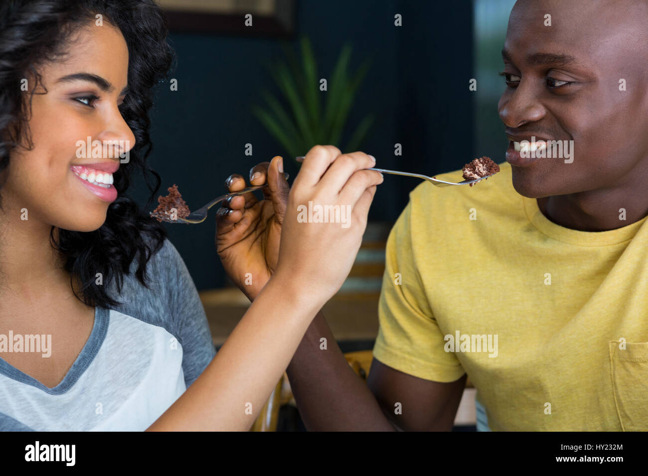 Smiling young couple feeding each other dessert in coffee shop - Stock Image