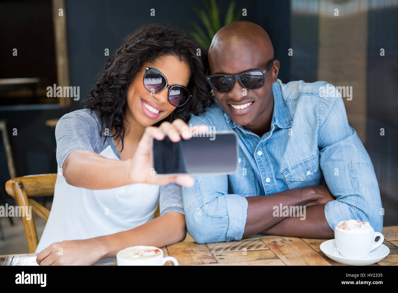 Smiling young couple taking selfie with smart phone in coffee shop Stock Photo