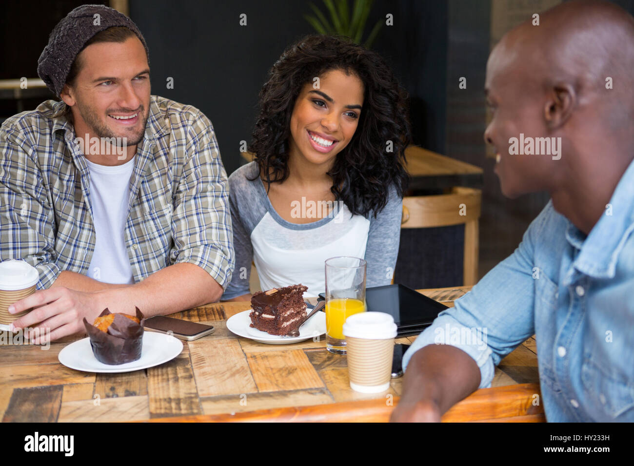 Happy multi ethnic friends talking at table in coffee shop - Stock Image