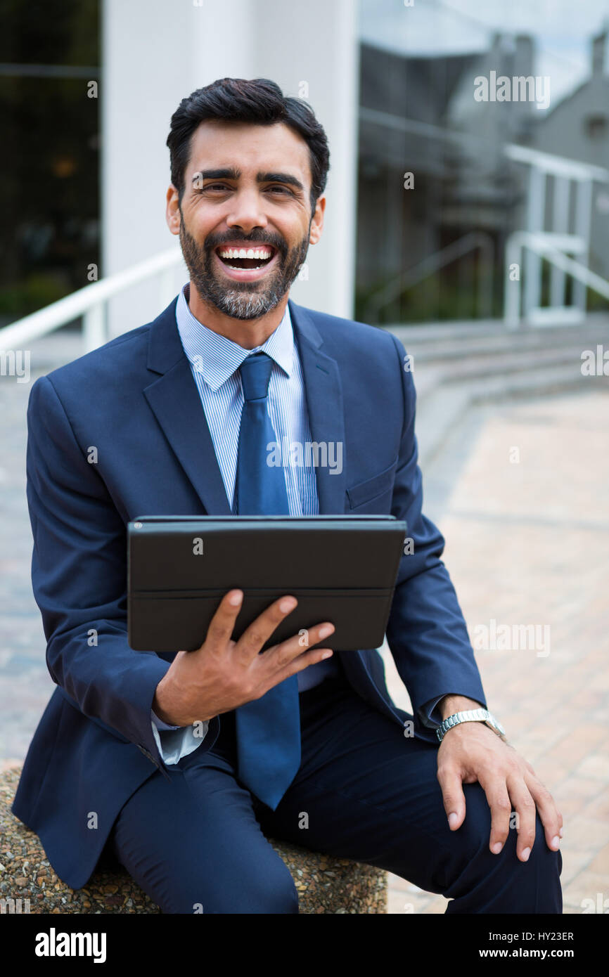 Smiling businessman using digital tablet in the office premises - Stock Image