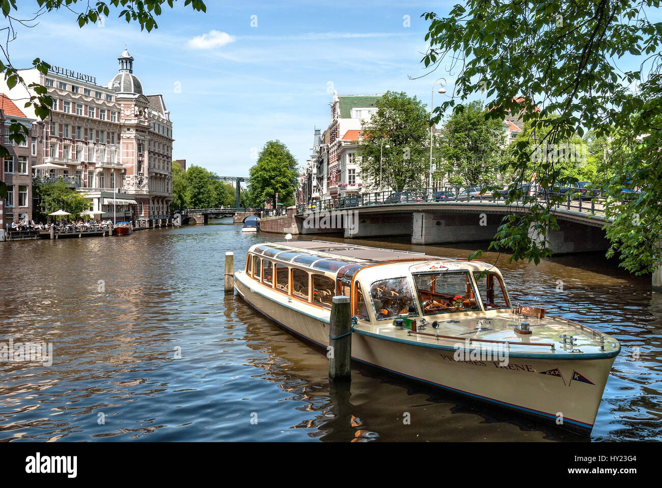 Sightseeing boat driving in a water channel in the inner city of Amsterdam, Holland. Stock Photo