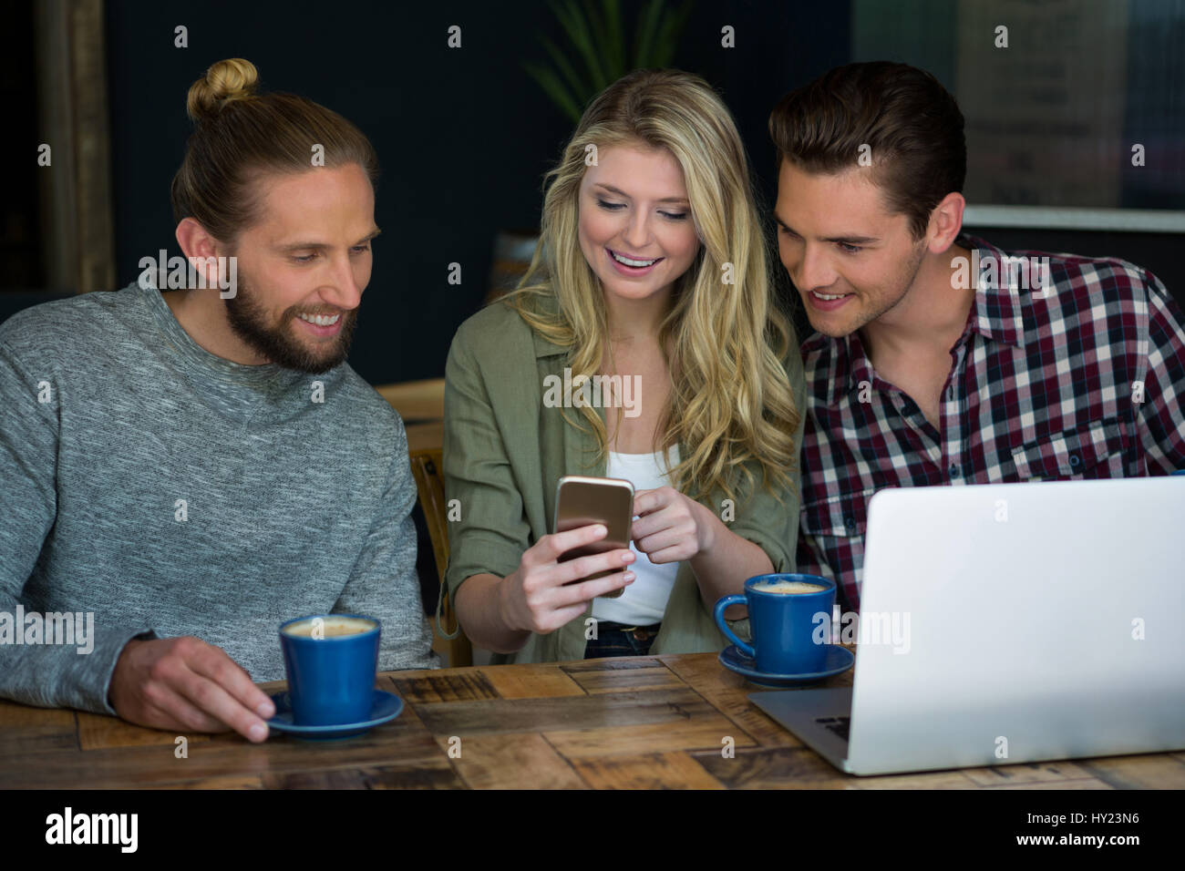 Smiling young friends using smart phone at table in cafeteria - Stock Image