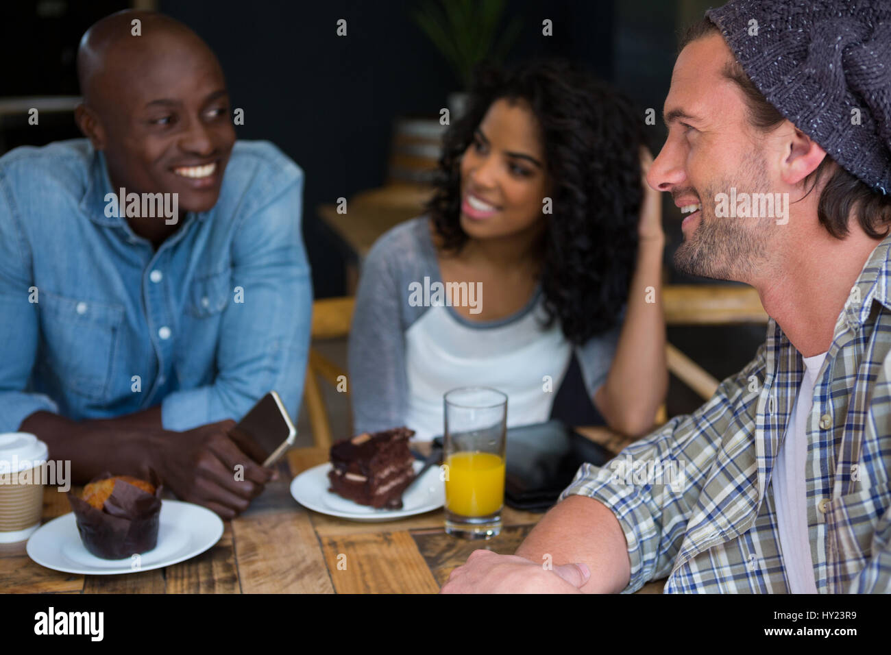 Happy young man talking with friends at table in coffee house Stock Photo