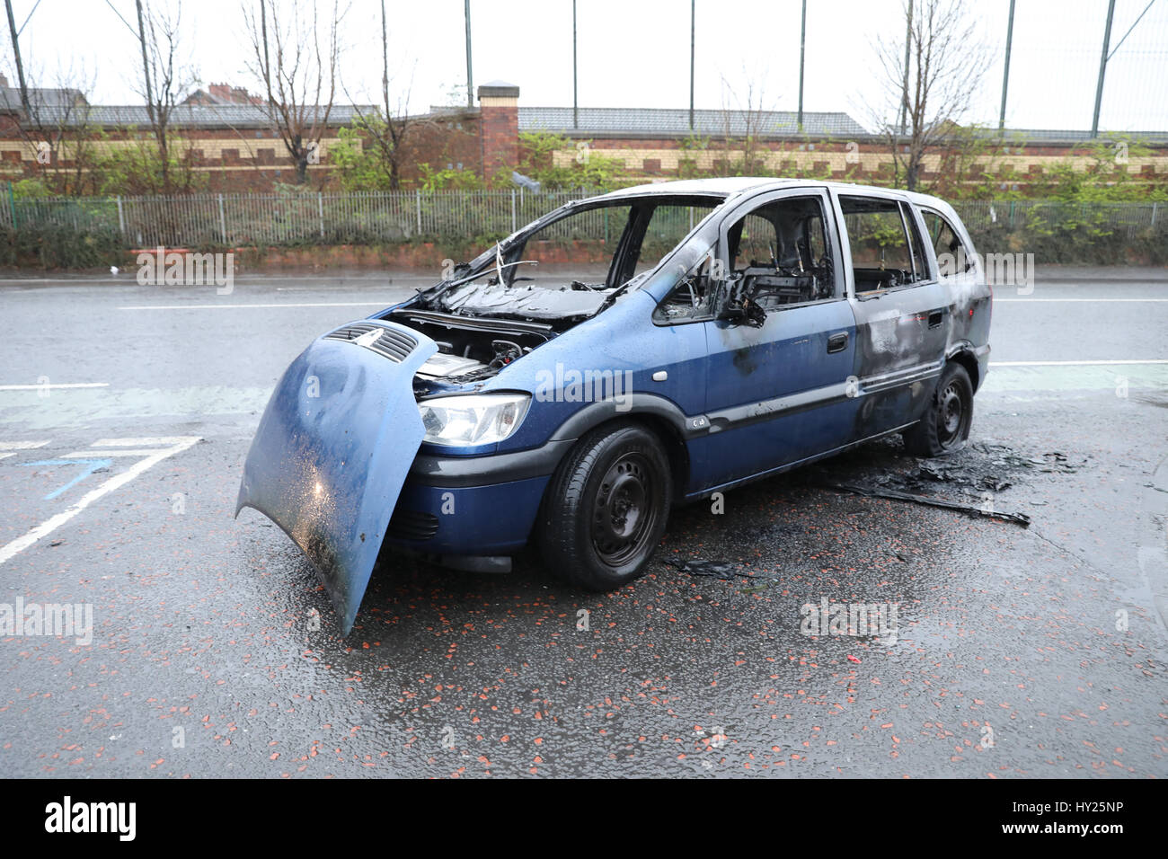 Belfast, Ireland. 31st March 2017. Stolen burnt out car next to Belfast peace wall Credit: Anthony Lynn/Alamy Live - Stock Image