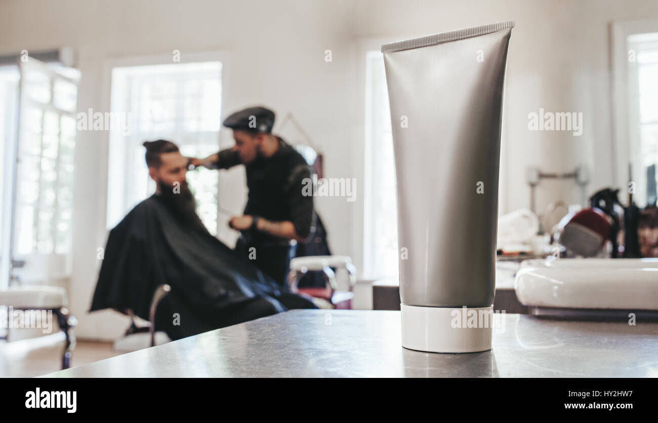 Shaving cream tube on counter with barber serving client in background. - Stock Image