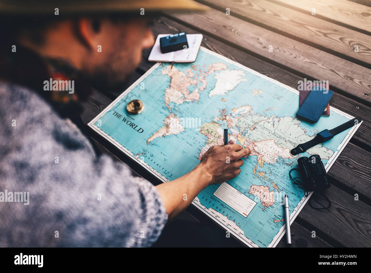 Tourist pointing at india on world map surrounded with binoculars tourist pointing at india on world map surrounded with binoculars compass and other travel accessories man looking at the world map sitting on woode gumiabroncs Image collections